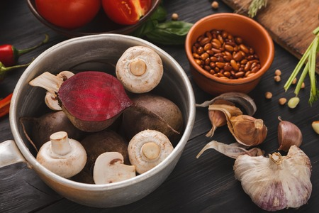 Mushrooms and beetroots in white bowl on wooden background. Healthy natural food on rustic wooden table. Garlic and grains beside