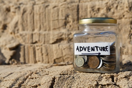 Glass jar with coins for adventure on rock background, copy space. Money box, distribution of cash savings concept. Stock Photo