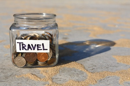 Glass jar with coins for travel on gray floor with sand background, copy space. Money box, distribution of cash savings concept. Stock Photo
