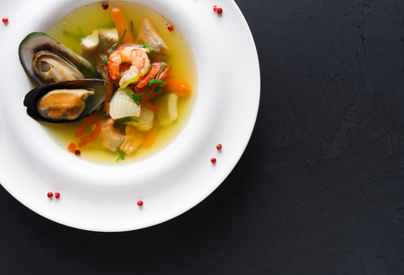 French cuisine restaurant. Seafood soup with white fish, shrimps and mussels in plate sprinkled with spices. Freshly cooked exclusive meals at black background with copy space, top view Stock Photo