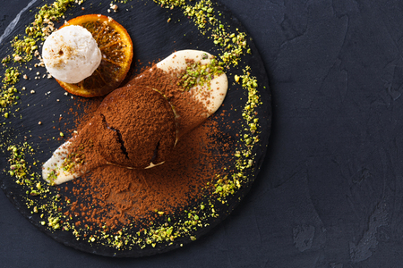 gateau: Exquisite dessert on black background. Chocolate fondant, creme anglaise and vanilla ice cream, sprinkled with cocoa on slate decorated with orange citron and pistachio crumble, top view, copy space Stock Photo