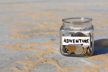 Glass jar with coins for adventure on gray floor with sand background, copy space. Money box, distribution of cash savings concept. Stock Photo
