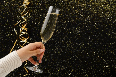 Celebrating new year, birthday, xmas party. Female hand with champagne flute and colorful tinsel on black backgroud with golden glitters, copy space. Mockup for postcard