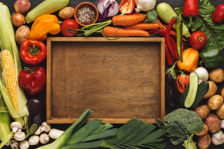 Fresh organic vegetables and wooden box with copy space background. Healthy natural food. Tomato, leek, carrot, pepper, potato and other cooking ingredients top view