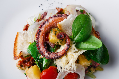 Salad with octopus and vegetables close up. Appetizing fresh mediterranean seafood meal with toasts, restaurant serving