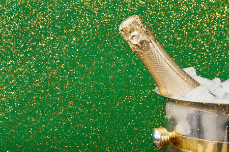 uncork: Celebrating new year, birthday, xmas party. Bottle of champagne in a bucket on green backgroud with glitters, copy space. Mockup for postcard