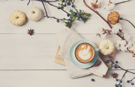 Pumpkin spice latte. Blue coffee cup with foam, cinnamon sticks, cotton plant and small yellow pumpkins at white wood background. Autumn fall hot drinks, cafe and bar concept, top view with copy space