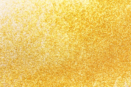Golden glitter texture abstract background, top view. Yellow dusty shimmer decoration, shiny and sparkling. Holidays and glamour concept.