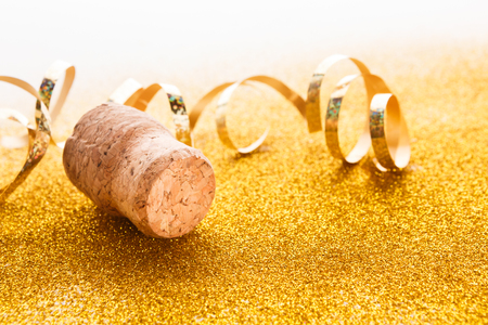 Champagne cork and golden serpentine on shiny glitter on white background, copy space. Happy New Year and Merry Christmas, celebration backdrop