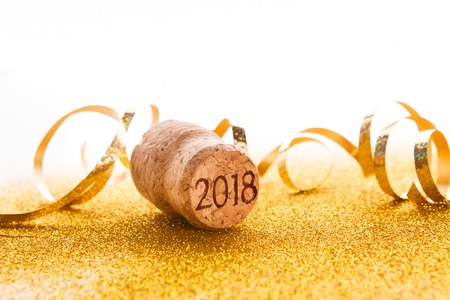 Champagne cork with 2018 stamp and golden serpentine on shiny glitter on white background, copy space. Happy New Year and Merry Christmas, celebration backdrop