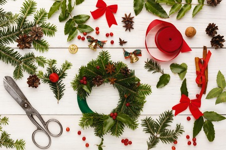Creative christmas diy. Making handmade craft xmas wreath. Home leisure, tools, trinkets, cup, details for holiday decorations on white wooden table. Top view Фото со стока