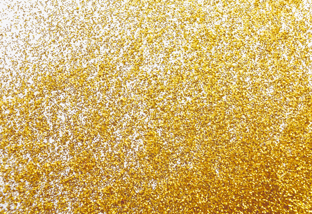 Golden glitter texture on white, abstract background, top view. Yellow dusty shimmer decoration, shiny and sparkling. Holidays and glamour concept.