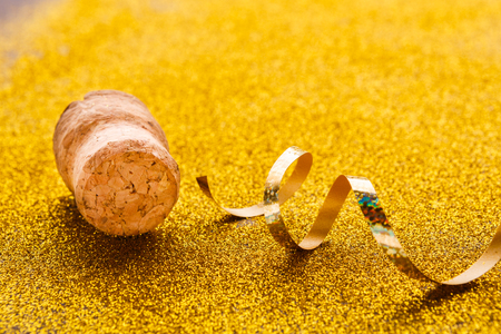 Champagne cork and golden serpentine on shiny glitter background closeup, copy space. Happy New Year and Merry Christmas, celebration backdrop