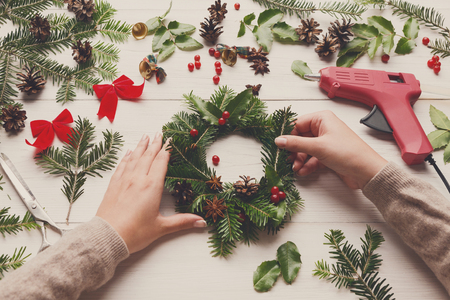 Creative leisure, tools and trinkets for xmas holiday decoration. Point of view of white wooden table background with glue gun, female hands making wreath
