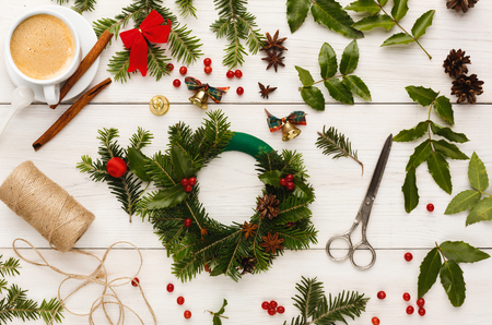 Creative christmas diy. Making handmade craft xmas wreath. Home leisure, tools, trinkets for holiday decorations, cup on white wooden table. Top view