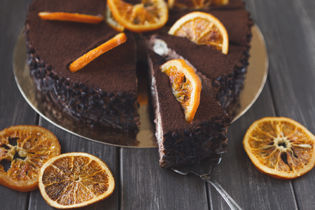 Chocolate cake with cream and profiterole, decorated with candied oranges. Traditional creamy dessert, copy space