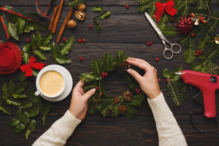 Creative leisure, tools and trinkets for xmas holiday decoration. Top view of dark wooden table background with female hands making wreath 스톡 콘텐츠