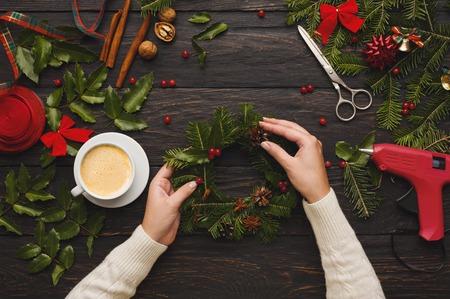Lazer criativo, ferramentas e bugigangas para a decoração do feriado de Natal. Vista superior do fundo da mesa de madeira escura com mãos femininas fazendo grinalda