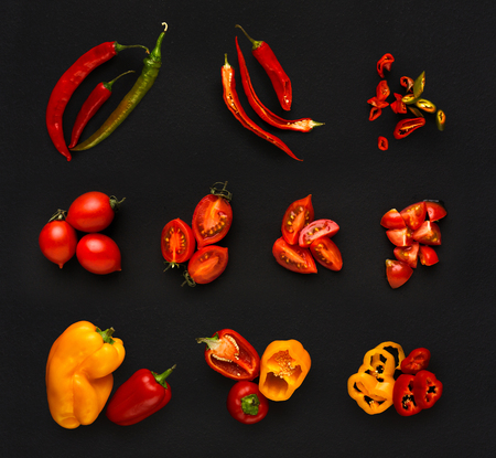 Collage of assorted red vegetables isolated at black background. Fresh raw whole and cut cooking ingredients. Chilli and bell pepper, cherry tomatoes top view