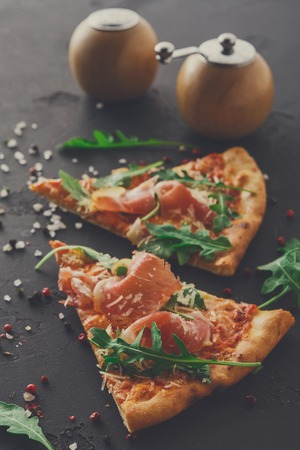 Slices of pizza with prosciutto and rocket salad with spices on black background, copy space, top view