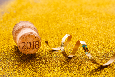 Champagne cork with 2018 stamp and golden serpentine on shiny glitter background closeup, copy space. Happy New Year and Merry Christmas, celebration backdrop