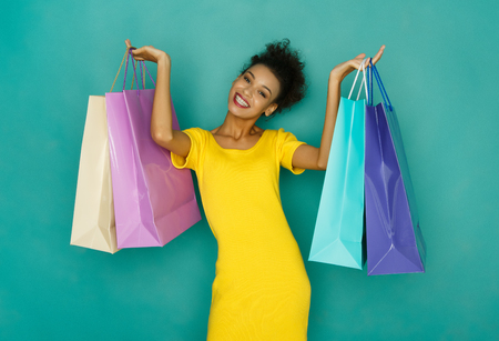 Happy mulatto girl with colorful shopping bags. Smiling shopaholic at turquoise sudio background with copy space
