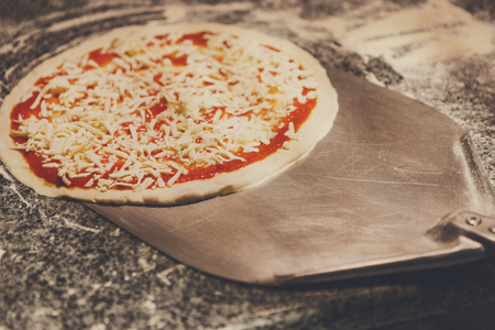 Taking raw pizza with metal shovel for baking in oven, copy space