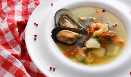 French cuisine restaurant. Seafood soup with white fish, shrimps and mussels in plate sprinkled with spices. Freshly cooked exclusive meals on white wood with checkered cloth and cutlery, closeup