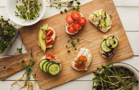 Vegetarian wholegrain sandwiches and bowls with micro greens assortment. Vegan party food table with organic vegetables canapes. Healthy lifestyle and eating right concept, top view