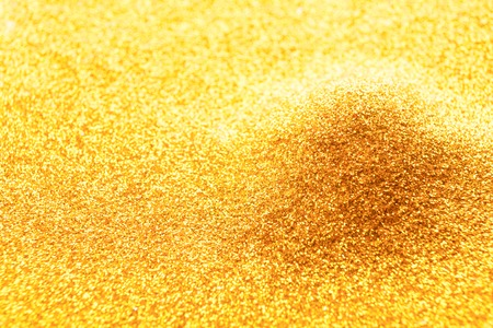 Golden glitter pile, handful spread, abstract luxury background with copy space. Yellow dusty shimmer decoration heap, shiny and sparkling. Holiday and glamour concept.