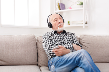 Dreamy senior man listening to music on smartphone with headphones, sitting on sofa at home, copy space Banque d'images