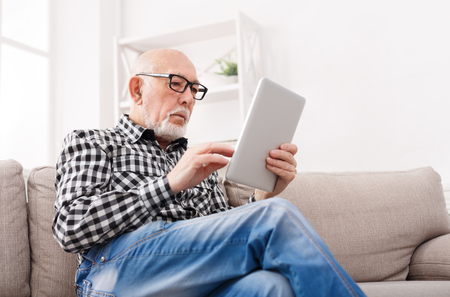 Senior man reading news on digital tablet. Mature male using portable computer at home, copy space