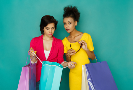 Happy multiethnic girlfriends with shopping bags. Two excited shopaholics boasting with purchases at turquoise sudio background with copy space