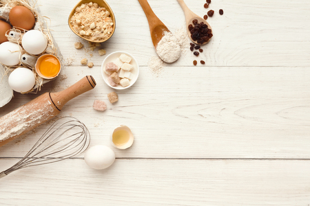 Cooking ingredients background. Border of flour, eggs, raisins, sugar and kitchen utensils on white rustic wood with copy space. Dough preparing and pastry concept, top view