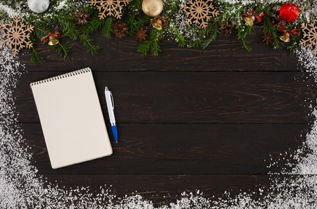 Blank notepad for wish list or letter to Santa at dark wooden table background decorated with snow and fir tree twigs garland, top view with copy space. Preparing for winter holidays concept