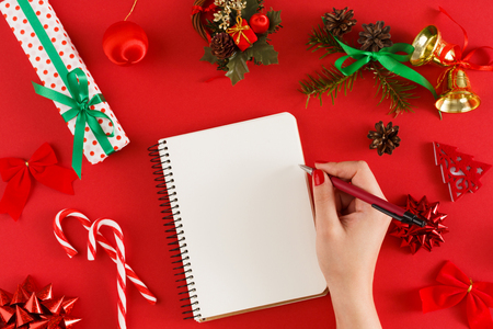 Women hands writing wish list for xmas. Christmas staff on red background with copy space on notebook. Point of view, crop