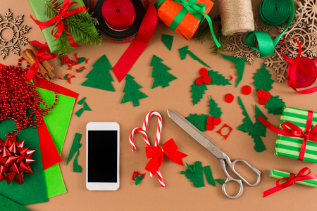 Christmas online shopping background. Cell phone on messy table with felt scraps, scissors, candy canes and decorations. Electronic devices, internet commerce on winter holidays concept. Banque d'images
