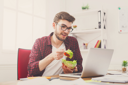 Young handsome businessman at working place has healthy lunch in office, diet and eating right concept. Stock Photo