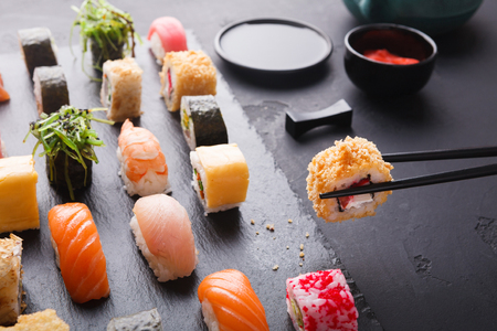 Eating sushi at restaurant. Chopstick taking roll with yellow tobiko, japanese cuisine, copy space