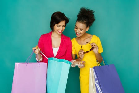 Happy smiling multiethnic girlfriends with colorful shopping bags. Two excited shopaholics boasting with purchases at turquoise sudio background with copy space