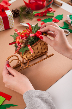 Making handmade craft christmas ornaments, sleigh with gift box, balls and spruce tree branch. Table with female hands and trappings. Creative diy hobby.
