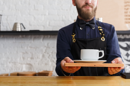 Smiling barman welcoming guests at coffee house counter. Portrait of young bearded man in uniform offering hot coffee cup. Small business, occupation people and service concept, copy space