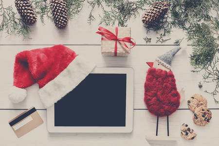 Christmas online shopping background. Tablet screen with copy space top view on white wood, credit card, present boxes and santa hat. Electronic devices, internet commerce on winter holidays concept