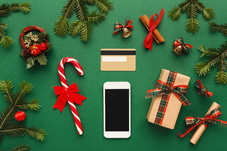 preparing for winter holidays background smartphone credit card and christmas decorations on green table