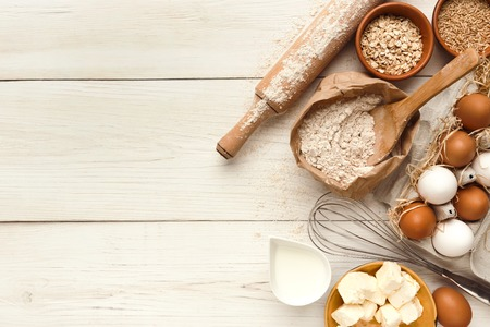 Cooking ingredients background. Border of flour, eggs, raisins, sugar, milk, butter and kitchen utensils on white rustic wood with copy space. Dough preparing and pastry concept, top view