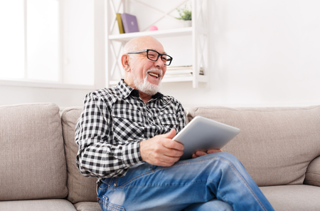 Smiling senior man reading news on digital tablet. Cheerful excited mature male using portable computer at home, copy space Stock Photo