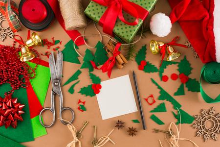 크리 에이 티브 DIY 공예 취미. 펠트 시트와 스크랩,가 위 및 trapping 공예 종이 배경 지저분한 테이블에 크리스마스를위한 인사말 카드의 장식. 홈 레저,