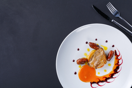 Roasted goose liver with date, apple and fruit and berry sauce painting with cutlery top view. Creative french cuisine, delicatessen restaurant meal Stockfoto
