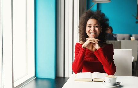 Happy smiling black girl at cafe table. Young woman enjoying hot coffee and reading favorite book, looking at camera. Leisure, education and urban lifestyle concept.