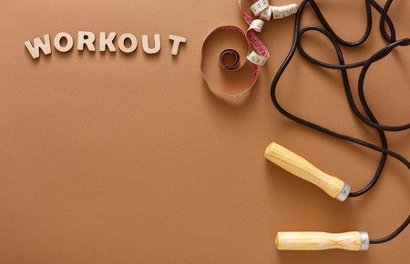 Workout word, jumping rope and measuring tape on brown background. Skipping rope, sport supply, weightloss, slimming concept